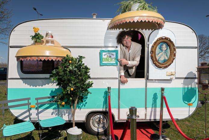 Rob Janssen in een caravan waarin een quarantaine-diner voor twee wordt geserveerd.