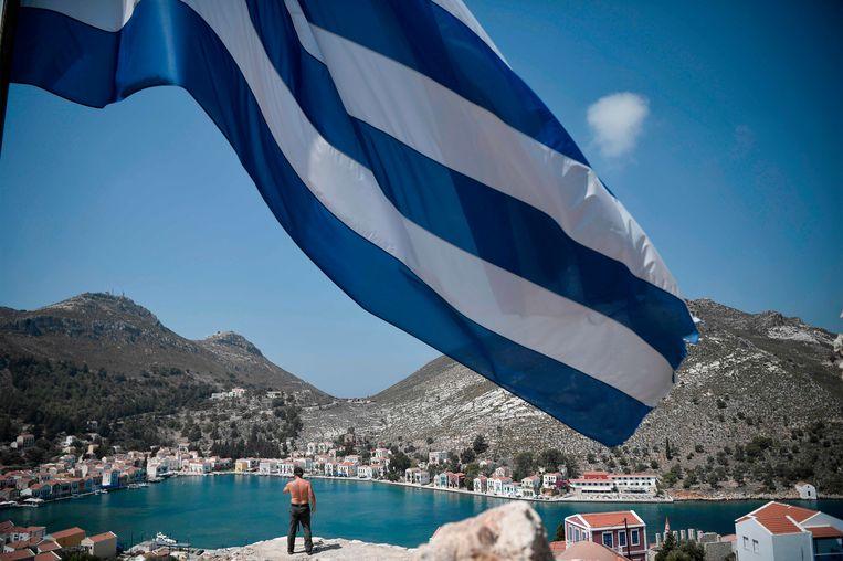 Een man kijkt uit over een inham van het Griekse eilandje Kastellorizo, op twee kilometer van de Turkse kust. Beeld Louisa Gouliamaki / AFP