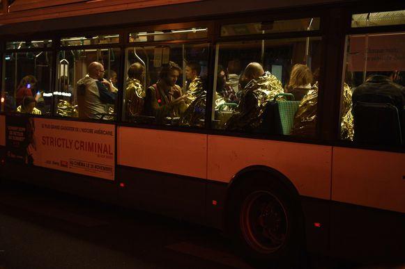 Concertgangers die de aanslag in de Bataclan hebben overleefd, worden in bussen weggebracht.