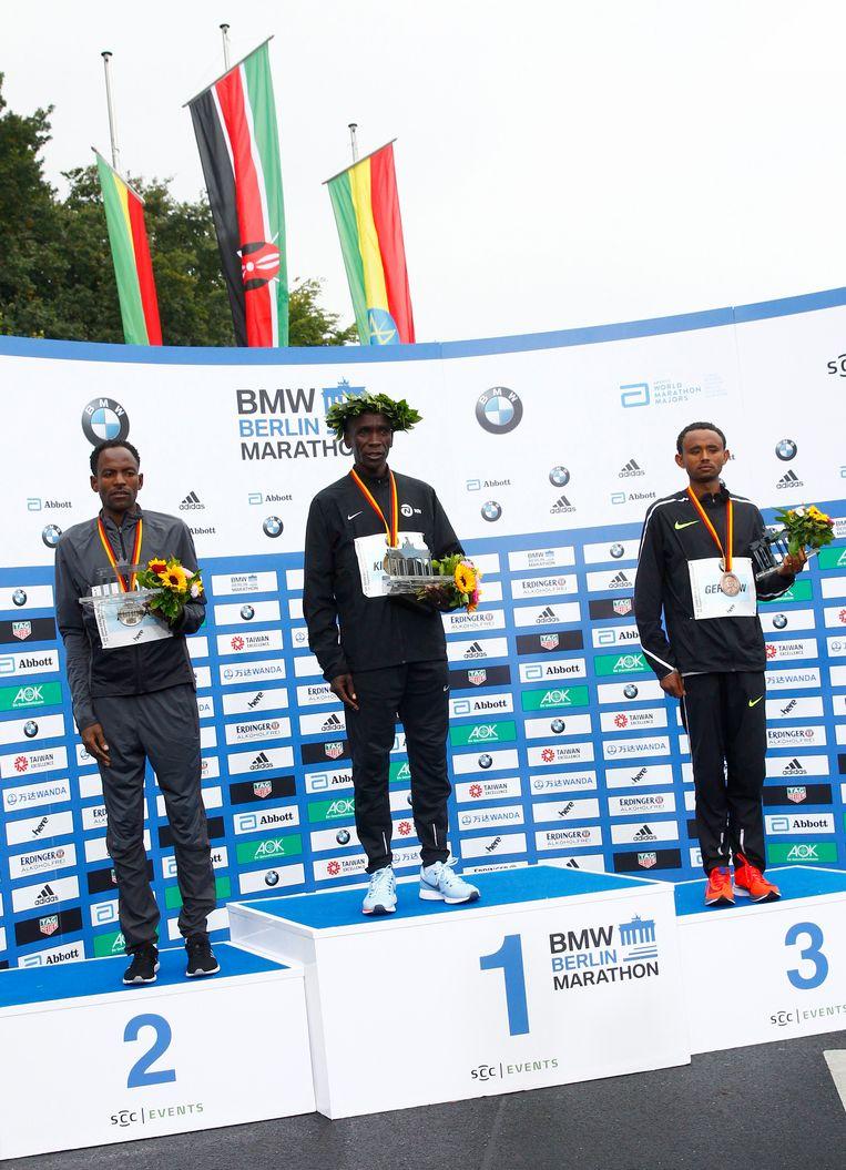 Guye Adola, Eliud Kipchoge en Mosinet Geremew op het podium Beeld afp