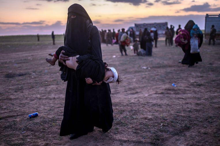 Een vrouw loopt met haar gewonde kind naar leden van de Syrische Democratische Strijdkrachten, net nadat ze het laatste IS-bolwerk Baghouz heeft verlaten. Beeld AFP