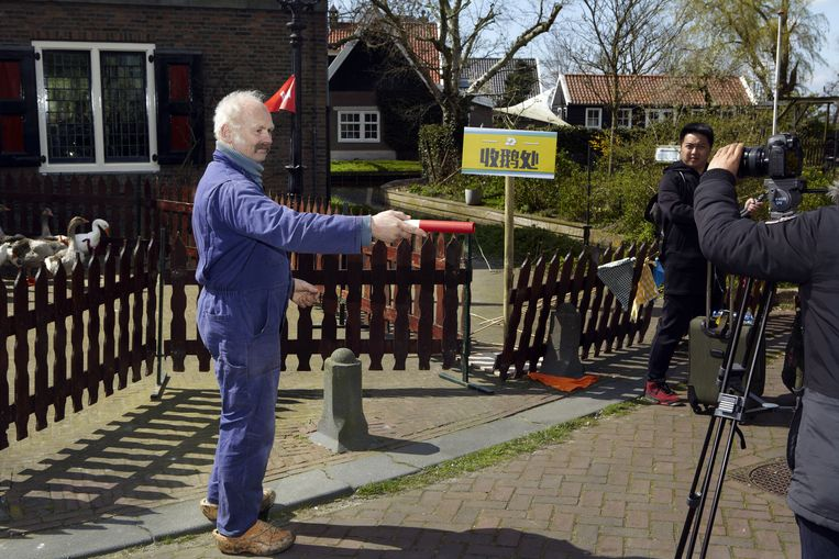 Veeboer Willem uit Ransdorp voorziet de Chinezen van een volgende spelopdracht. Beeld Jan Dirk van der Burg