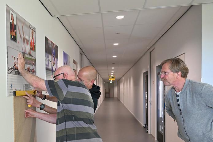 Personeel druk met het ophangen van de foto's voor de Wall of Fame, Jan Kottink kijkt toe.