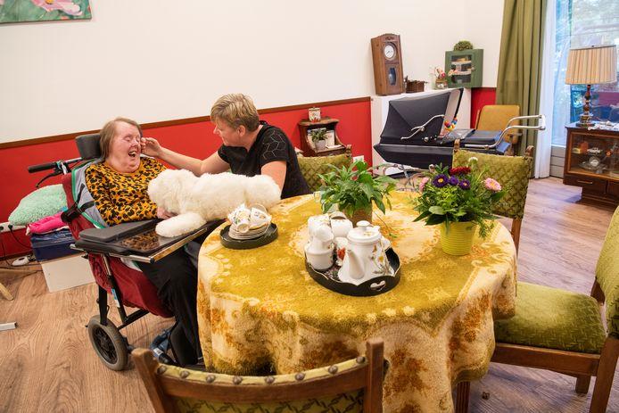 Begeleidster Kirstin van Essen heeft een persoonlijk moment met bewoonster Rineke. In een aantal woningen is een nostalgisch hoekje ingericht. Tegelijk zijn er volop moderne technieken in gebruik, zoals robot-knuffels.