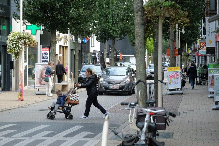 Een vrouw steekt met haar kind de winkelstraat over terwijl een auto nadert. Er gaan stemmen op om de straat autovrij te maken.