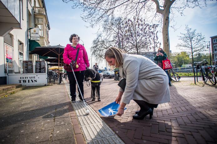 Martien Louwers plakt in aanwezigheid van Marjolein van den Broek en haar hond Harvey een sticker naast de geleidelijn