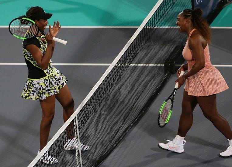 Venus (l) klopt haar jongere zus Serena in Abu Dhabi.