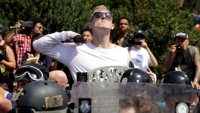 Een demonstrant maakt een snijgebaar bij zijn keel tijdens de extreemrechtse mars in Charlottesville.