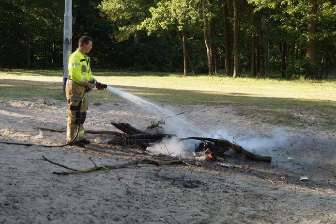 De brandweer doofde de smeulende boomstammen aan de oever van de Roeivijver in Drunen.