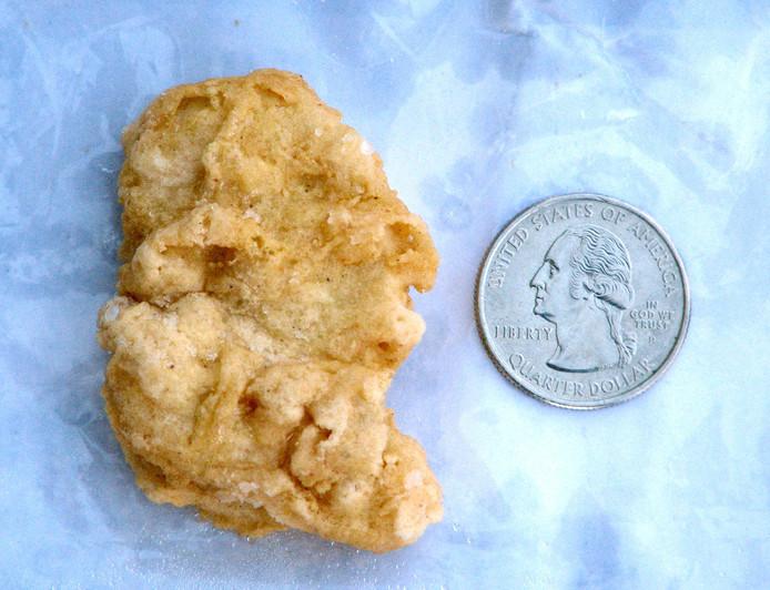De McNugget naast een kwartje met de afbeelding van George Washington.