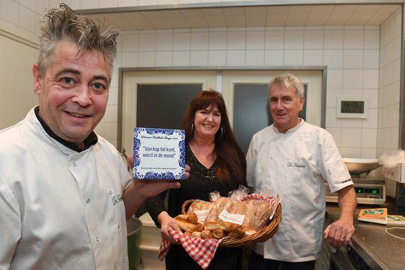 Ramon Ligthart (links) met het gewonnen tegeltje voor de slechtste slogan van het jaar. Op de achtergrond zijn vriendin Tineke de Wit en oud-bakker André Leurs, die meehelpt met het maken van de worstenbroodjes.