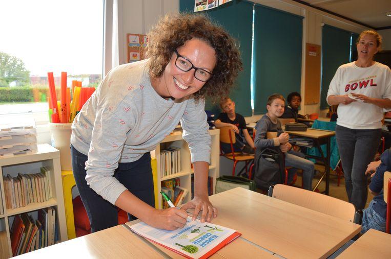 Juf Fien van het vijfde leerjaar van basisschool Molenveld tekent het Klimaatcharter.