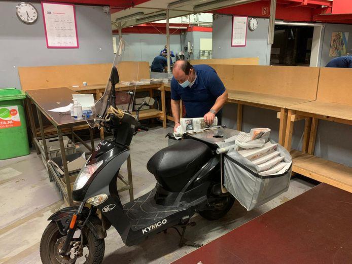 Michael Dogan, krantendepothouder in Den Haag, vult zijn tassen met kranten.
