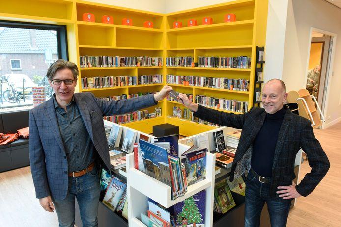 Wethouder Toon Bosmans (links) krijgt bij de opening van de nieuwe bibliotheek een lidmaatschapspas van directeur Luc Pruijn van bibliotheek Dommeldal.
