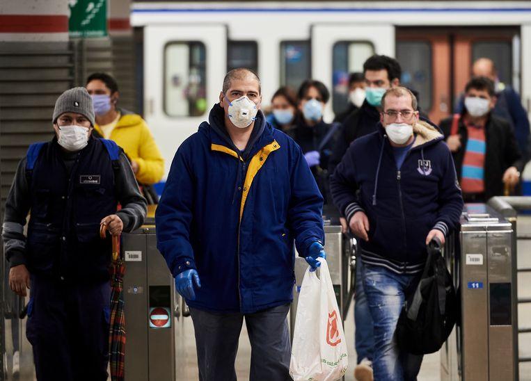 Bemaskerde Madrilenen op weg naar hun werk in een metrostation.  Beeld Getty Images