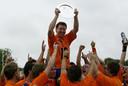 Oranje Zwart kampioen na winst op Bloemendaal, Jay Stacy op de schouders met kampioensschaal.