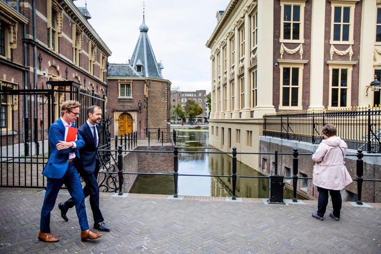 Minister Eric Wiebes loopt met zijn woordvoerder naar de auto na de vrijdagse ministerraad. Hij is een van de weinige VVD'ers die echt in de klimaatdoelstellingen gelooft. Beeld Freek van den Bergh