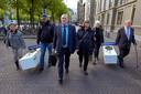 Nabestaanden van de vermoorde Piet Holskens en Hans Martens lopen met doodskisten bij de tweede kamer voor de actie: Moord mag niet verjaren.  Met koffer: Jan Holskens. Met petje en snor: Pieter Althuizen.
