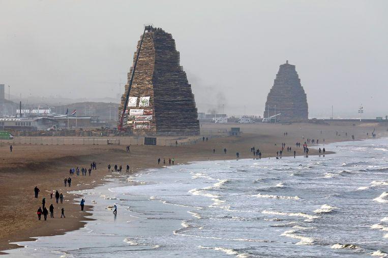 Opbouw van de vreugdevuren op het strand van Scheveningen (links) en Duindorp, december 2018. Beeld Dick Teske