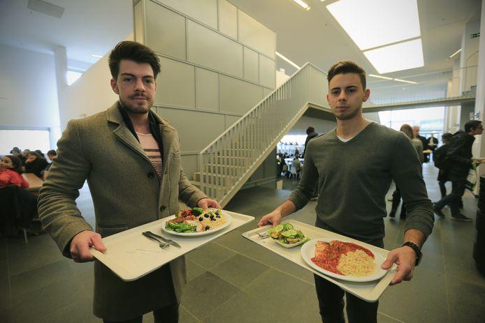 """Frederic Exelmans en Leroy Castermans met hun bord vol groenten, kip en zalm. """"Wij eten vaak gezond, dus de frieten missen we niet erg."""""""