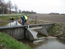 Een peilbeheerder van waterschap Brabantse Delta laat water in om de grondwaterstand omhoog te brengen.