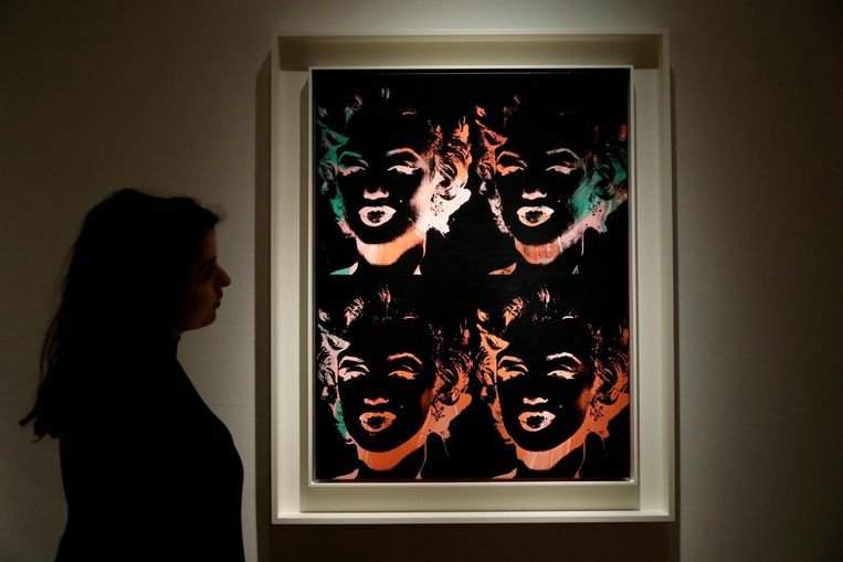 Een medewerkster van het veilingshuis bekijkt een kunstwerk van Andy Warhol. Beeld ap