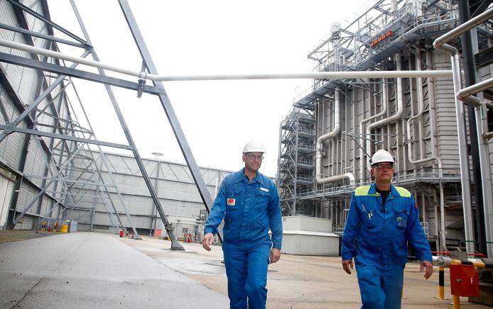 Coen Vervaeck (links) en Dennis Jansen op het Elsta-bedrijfsterrein, met links de 25 meter hoge geluidswand die het bedrijf omringt, en rechts één van de fornuisinstallaties.