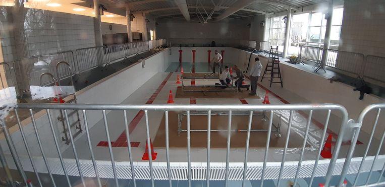 Een gespecialiseerde firma is begonnen met het stutten van het binnendak, vanop de vloer van de leeggepompte zwembadkuip.