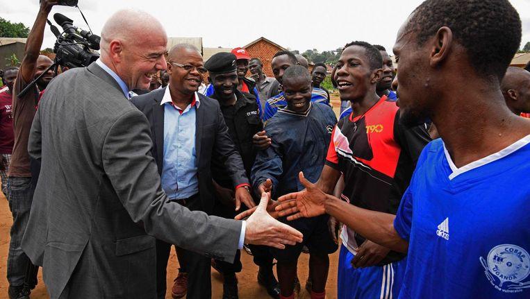 Gianni Infantino (l) schudt handen van Ugandese voetballers tijdens zijn rondreis door Afrika Beeld AFP