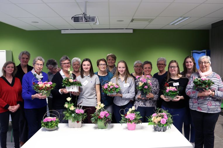Scholieren en senioren met het resultaat van een namiddag bloemschikken