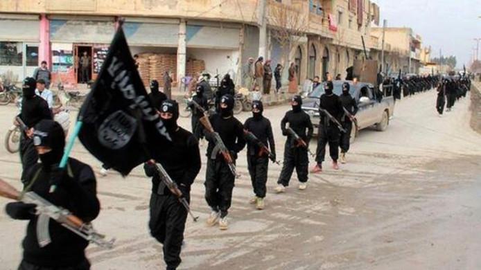 IS-strijders trekken door de straten in Raqqa, tot medio 2017 de hoofdstad van het kalifaat.