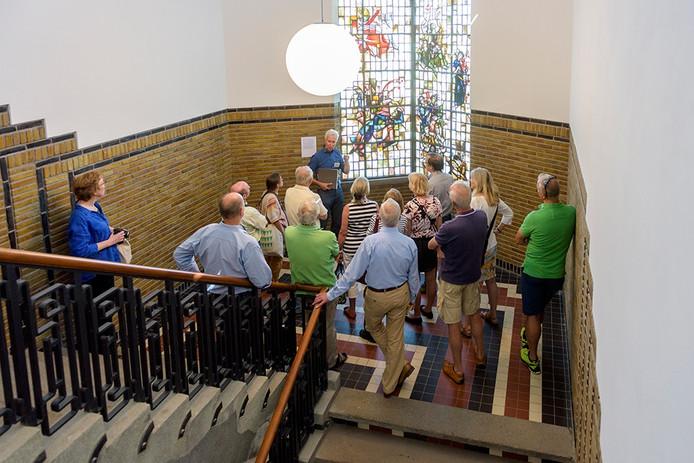 Bezoekers krijgen uitleg over de glas-in-loodramen in het trappenhuis van de Admirant in Eindhoven.