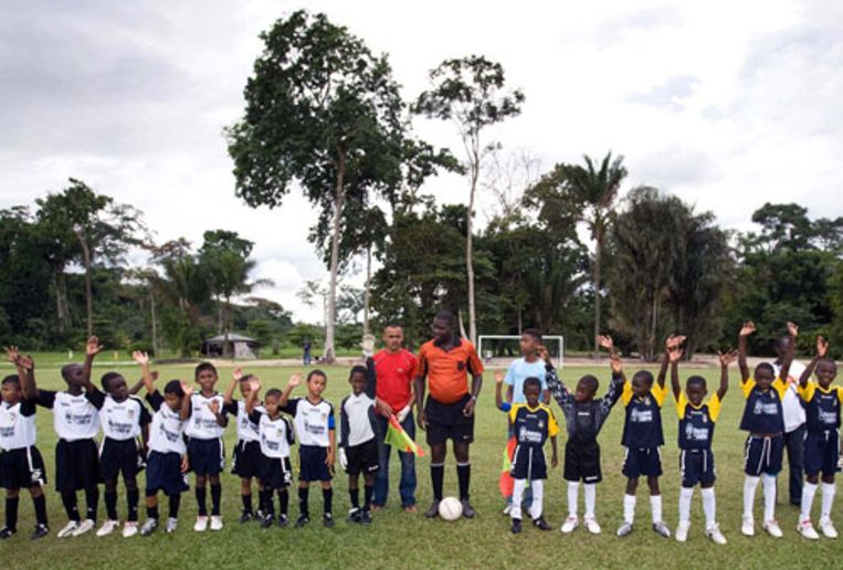 Surinaamse voetballertjes groeten het publiek voorafgaand aan een wedstrijd uit de comptetitie die door Clarence Seedorf is gepubliceerd. (Guus Dubbelman / de Volkskrant) Beeld