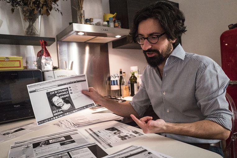 Raffaele Ariano in zijn flat in Milaan met een stapel bedreigingen die hij via Facebook ontving.  Beeld Zolin Nicola