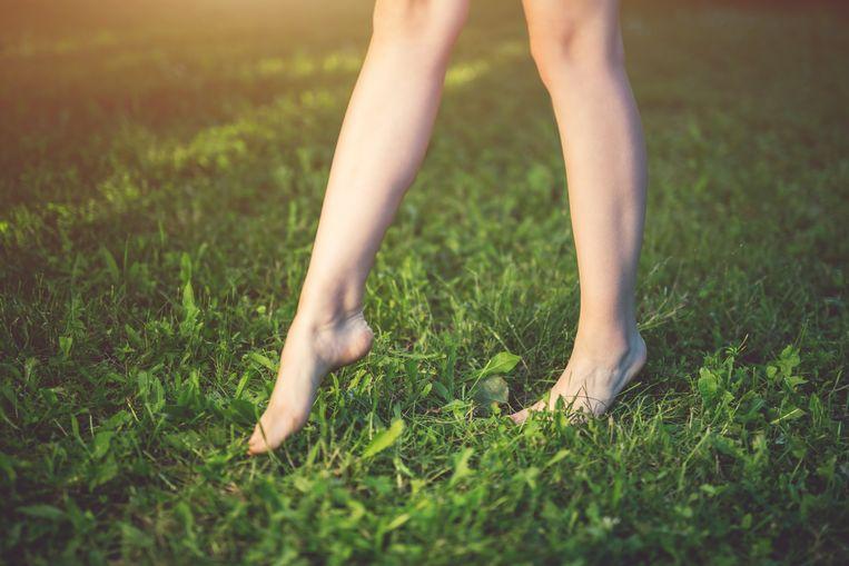 Voeten van jonge vrouw op groen gras.