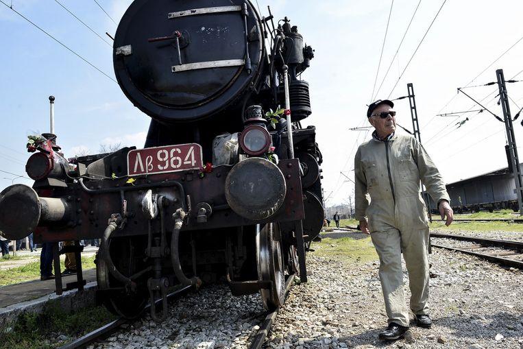 Een medewerker van de Griekse spoorwegen loopt langs de locomotief die gebruikt werd om Griekse Joden naar Auschwitz te sturen. Beeld ap