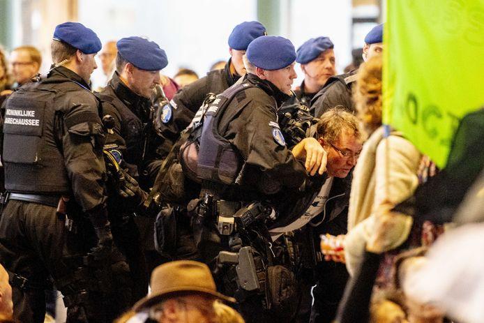 De Koninklijke Marechaussee verwijdert een actievoerder uit Schiphol Plaza.