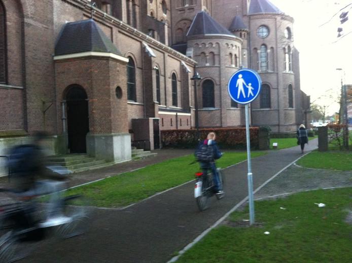 Scholieren fietsen nog steeds gewoon over het Kerkpaadje in Uden. Officieel mag dat niet meer.