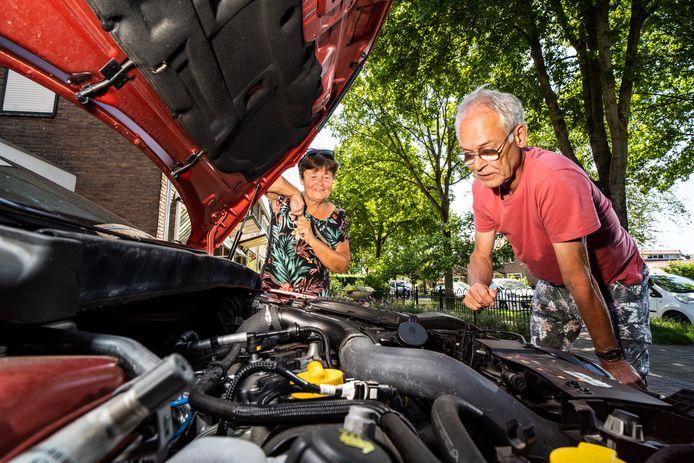 Gerard Jeurissen inspecteert de boel onder de motorkap van zijn auto. Buurvrouw Marjan Mölenberg kijkt toe.
