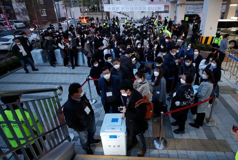 Een Koreaanse kiescommissie brengt een stembus met uitgebrachte stemmen. In Zuid-Korea slaagt de regering er zonder lockdown goed in de epidemie te beperken. De regeringspartij werd daarvoor woensdag beloond door de kiezers. Beeld AP