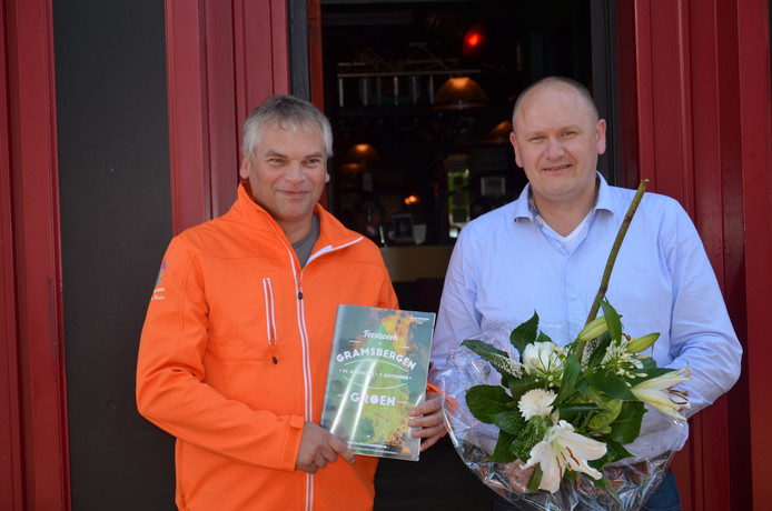 Henny Alfring ontvangt het eerste exemplaar van de feestgids voor Gramsbergen Lichtstad 2016 uit handen van de Oranjevereniging.