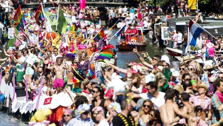 Boten varen over de grachten van Amsterdam tijdens de botenparade van de Gay Pride. Beeld null