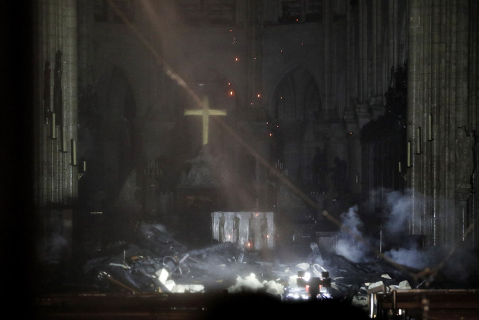 De binnenkant van de Notre-Dame. Vonken vallen van het dak naar beneden, waar een kruis hel oplicht tussen de geblakerde puinhopen.