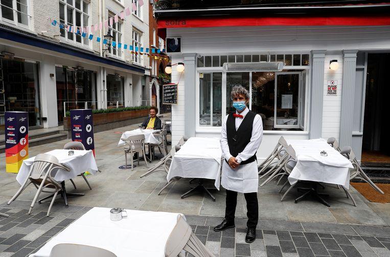 Een bediende wacht buiten een restaurant in Londen, na de heropening ervan. Beeld Reuters