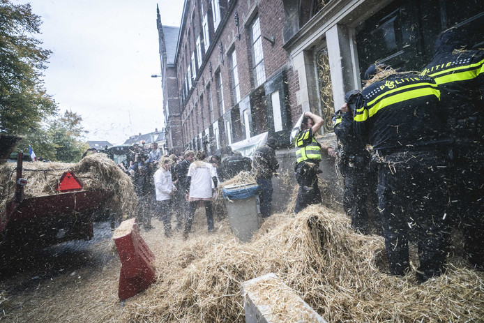 Politieagenten worden belaagd met stro tijdens het boerenprotest voor het provinciehuis in Groningen.