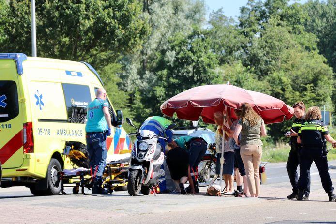 Ambulancepersoneel aan het werk na de valpartij op de Lossersestraat. Een parasol zorgt voor wat schaduw in de verzengende hitte.