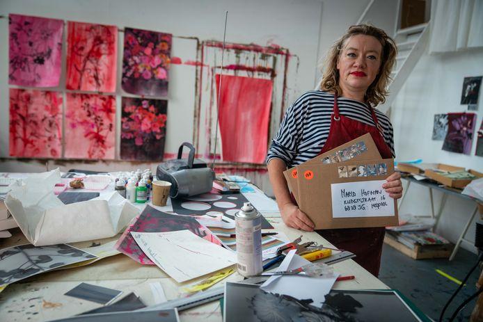 Kunstenares Anook Cléonne deelt kunstwerken uit.