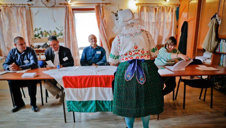 Een Hongaarse vrouw ontvangt een stembiljet voor het referendum Beeld ap