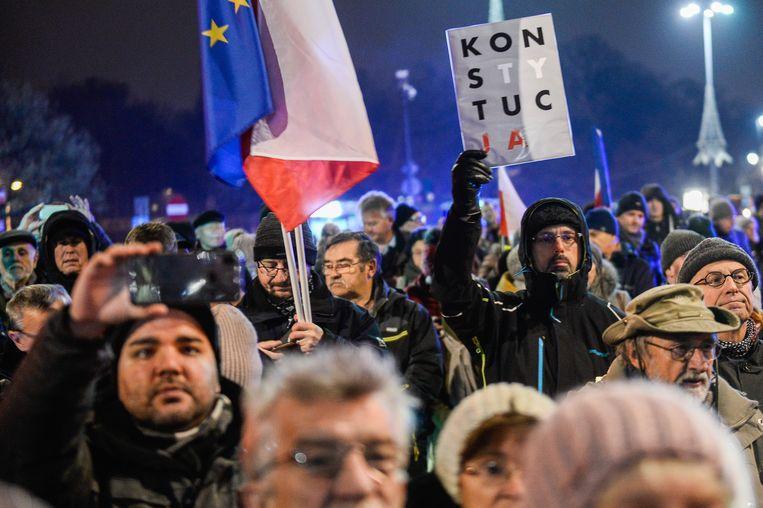 Een man houdt een protestbord met de tekst 'grondwet' omhoog tijdens een demonstratie voor het Poolse ministerie van justitie. Beeld Getty Images