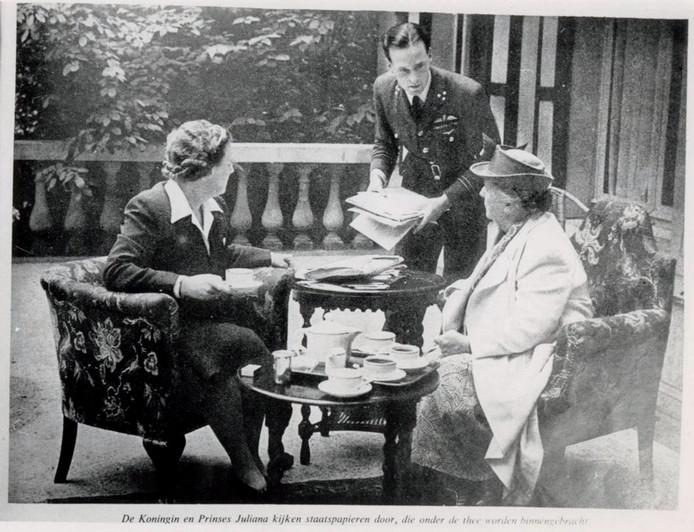 Koningin Wilhelmina en prinses Juliana drinken thee op het terras van Anneville terwijl Erik Hazelhoff Roelfzema papieren ter bestudering brengt.